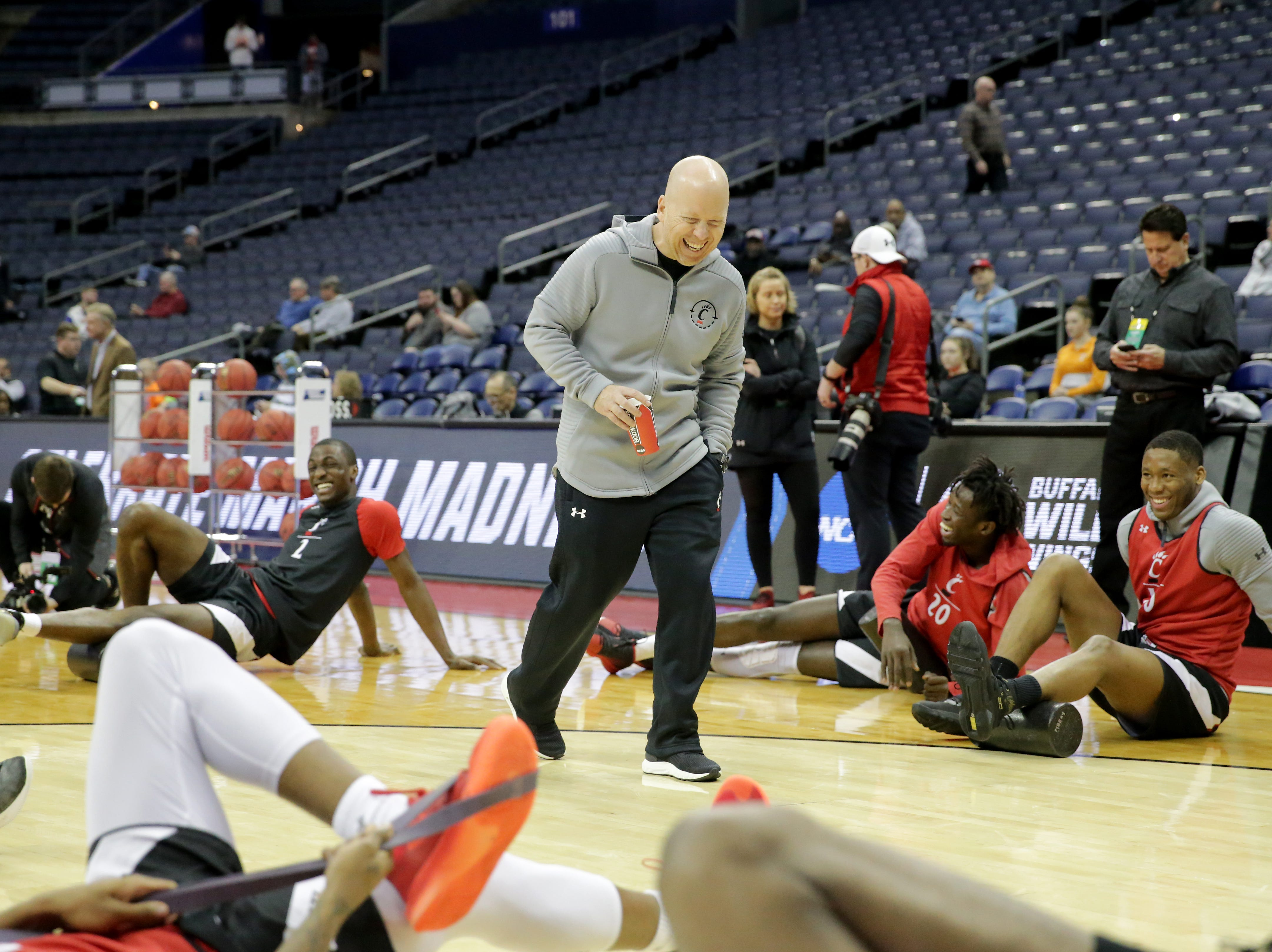 Cincinnati Bearcats head coach Mick Cronin shares a laugh with the team during stretch before open practice, Thursday, March 21, 2019, at Nationwide Arena in Columbus, Ohio.
