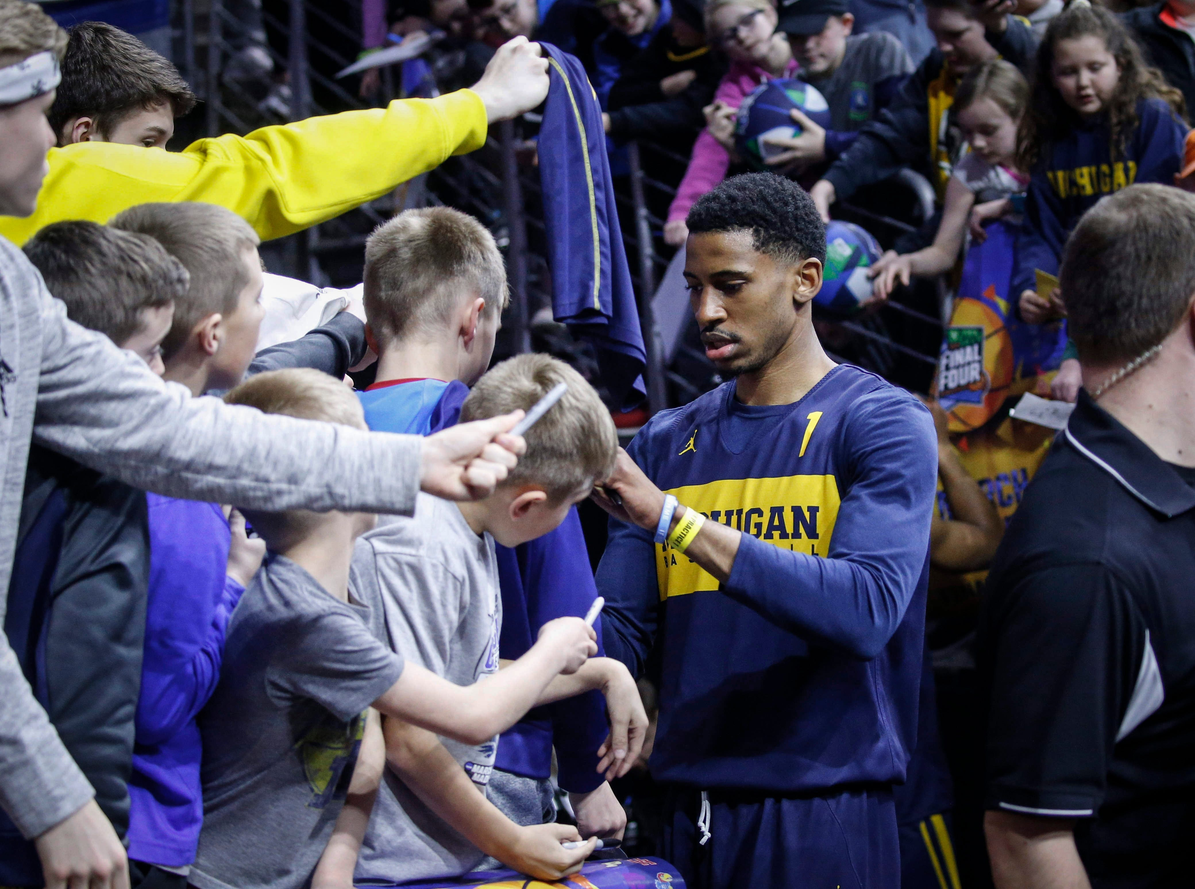 Michigan senior Charles Matthews signs autographs for fans after practice on Wednesday, March 20, 2019, at Wells Fargo Arena in Des Moines, Iowa.