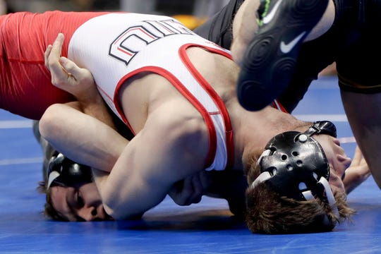 Iowa's Spencer Lee, left, and Northern Illinois' Bryce West grapple during a 125 pounds weight class match in the first round of the NCAA wrestling championship, Thursday, March 21, 2019, in Pittsburgh. (AP Photo/Keith Srakocic)