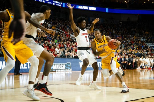 Minnesota's Dupree McBrayer (1) dribbles around Louisville's Darius Perry (2) during their NCAA Division I Men's Basketball Championship First Round game.