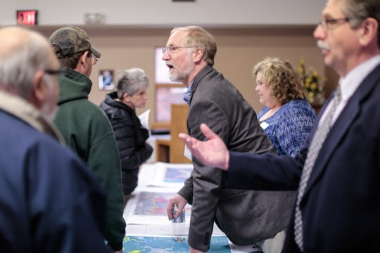 Robert Delaney of Michigan Department of Environmental Quality speaks with Oscoda residents during an open house meeting regarding the contamination at the former Wurtsmith Air Force Base along with other members of MDEQ, the Michigan Department of Health and Human Services, the Air Force, and the local health department on Wednesday March 23, 2016 at the Oscoda United Methodist Church in Oscoda to discuss how it effects residents.