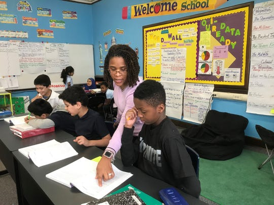 Kenya Posey, who teaches fourth-grade English language arts and social studies, works with students during a recent lesson.