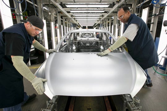 Two UAW workers at GM's Orion Assembly plant where GM builds its Bolt EV and the self-driving test cars.