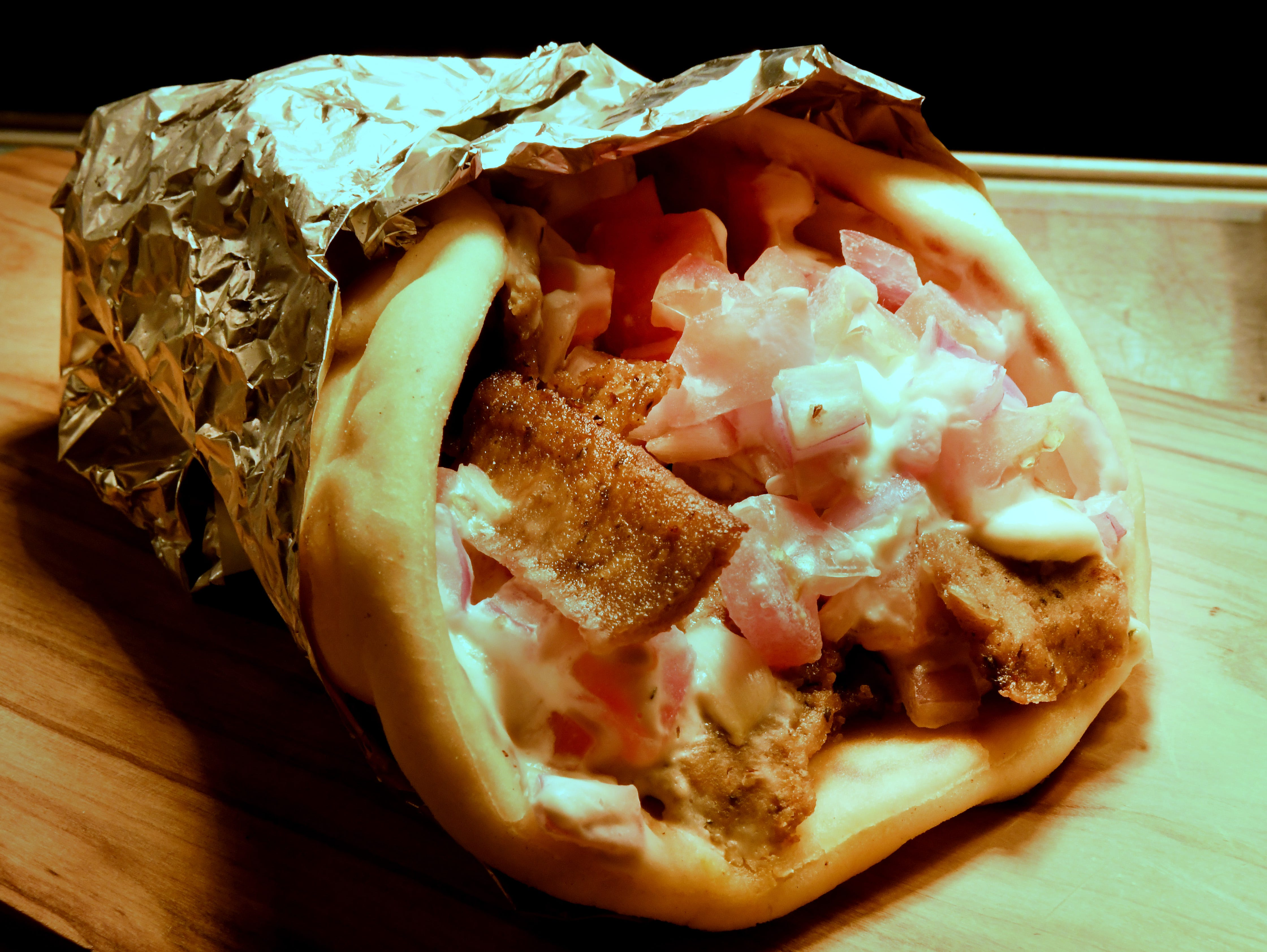 """""""Hand Carved Gyro"""" consisting a a soft pita filled with sizzling cared gyro meat, diced tomatoes, tzatziki saucer and red onion."""