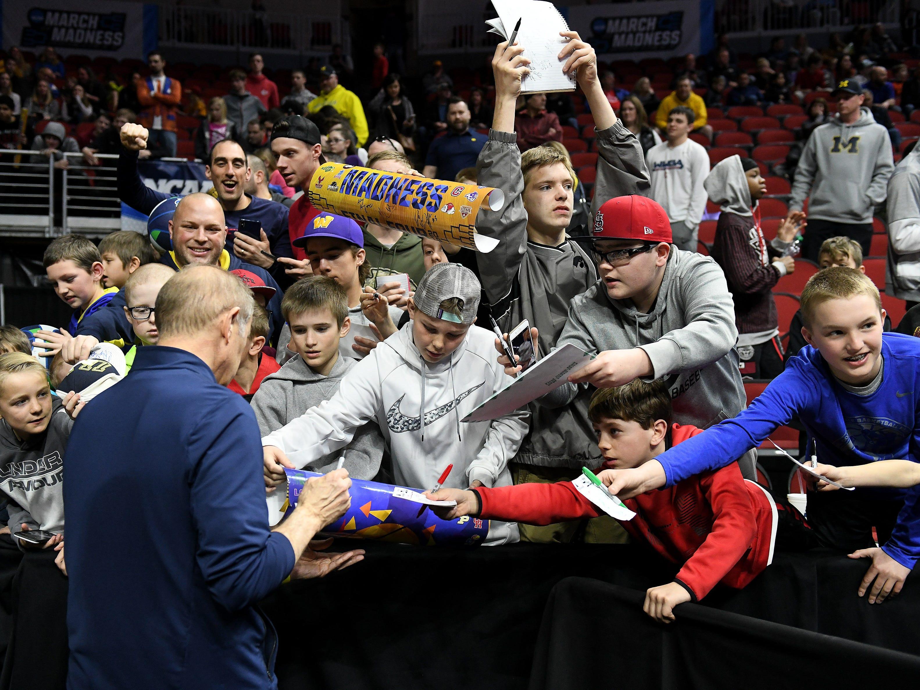 Michigan head coach John Beilein signs autographs.