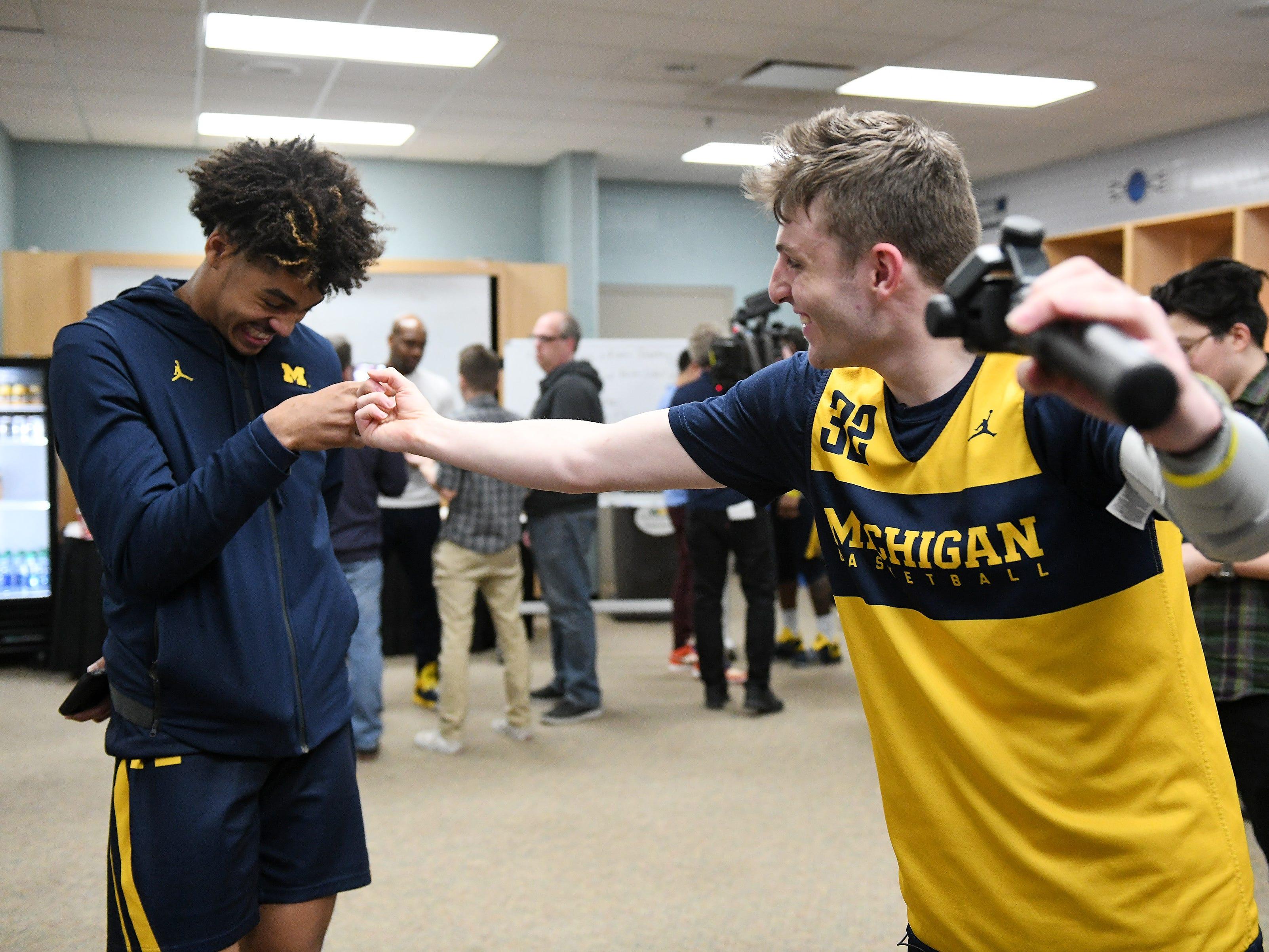 Michigan guard Luke Wilson jokes with guard Jordan Poole while Wilson is shooting video.