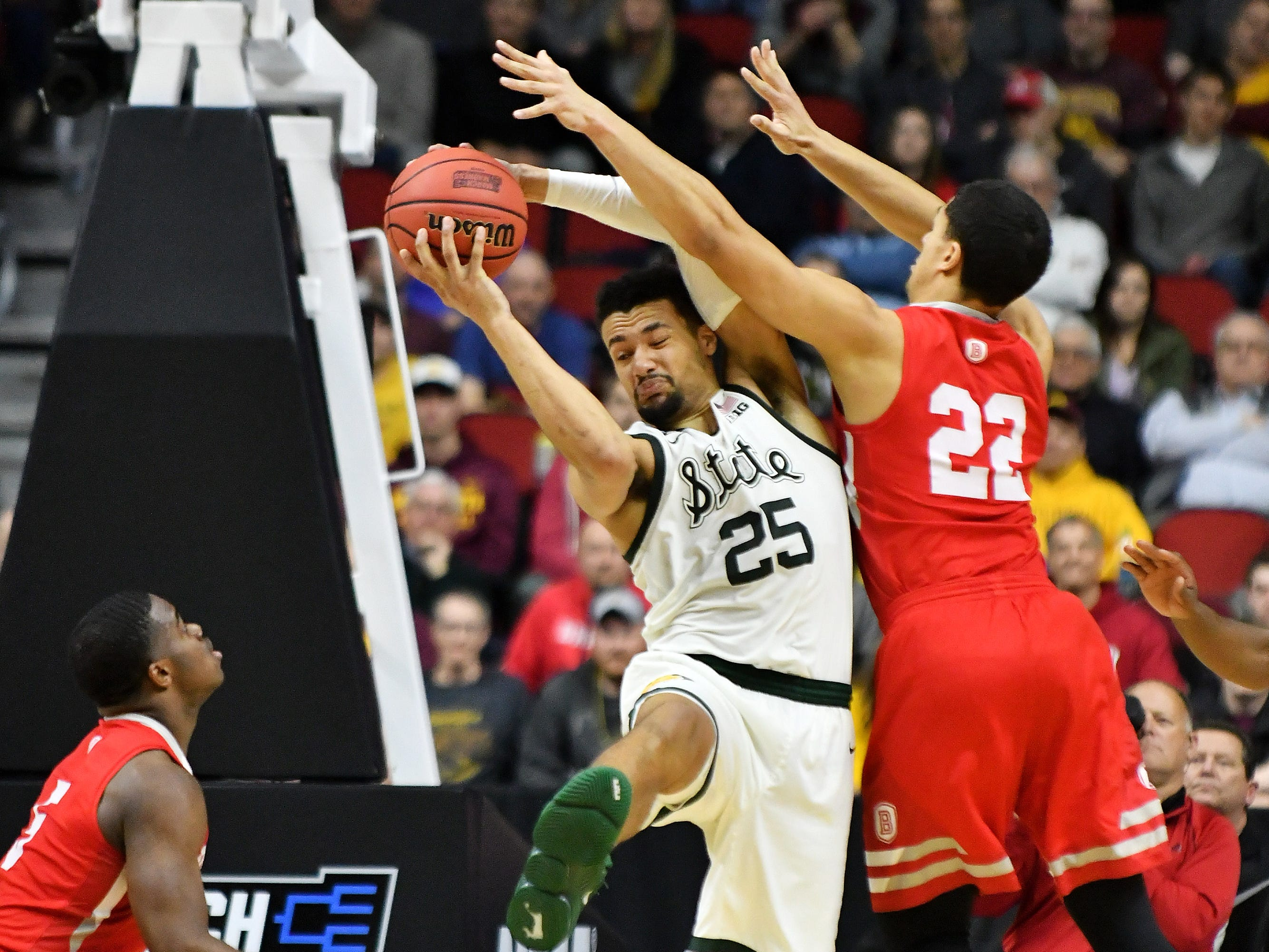 Michigan State forward Kenny Goins (25) comes up with a rebound between Bradley guard Ja'Shon Henry (22) and guard Darrell Brown, left, in the second half.