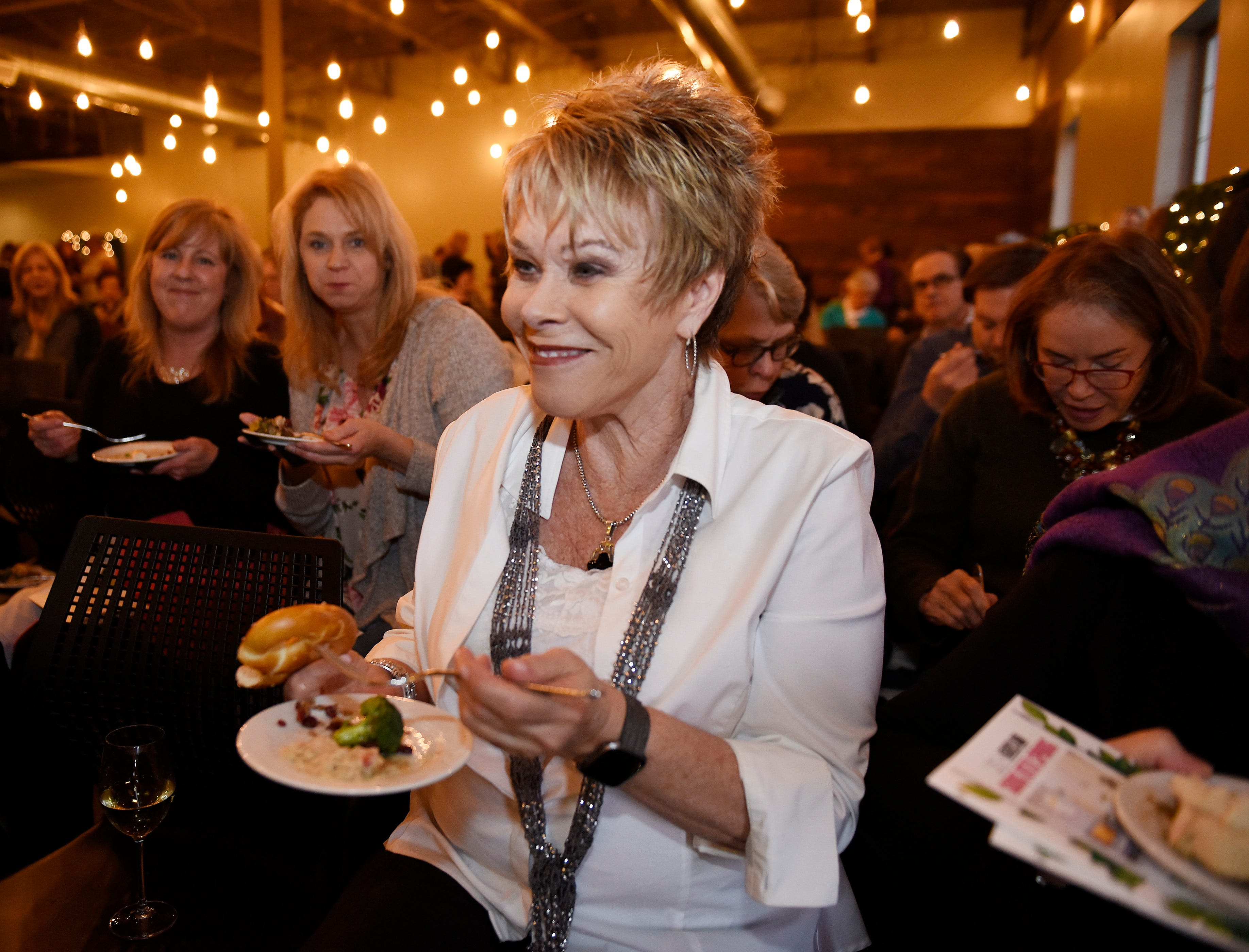 Dianne Weiss of Farmington Hills, taste a sample of food before the start of the event.