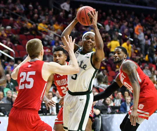 Bradley guard Nate Kennell (25), Bradley forward Elijah Childs, right, and Bradley guard Dwayne Lautier-Ogunleye (23), rear, converge on Michigan State guard Cassius Winston (5)  in the first half.
