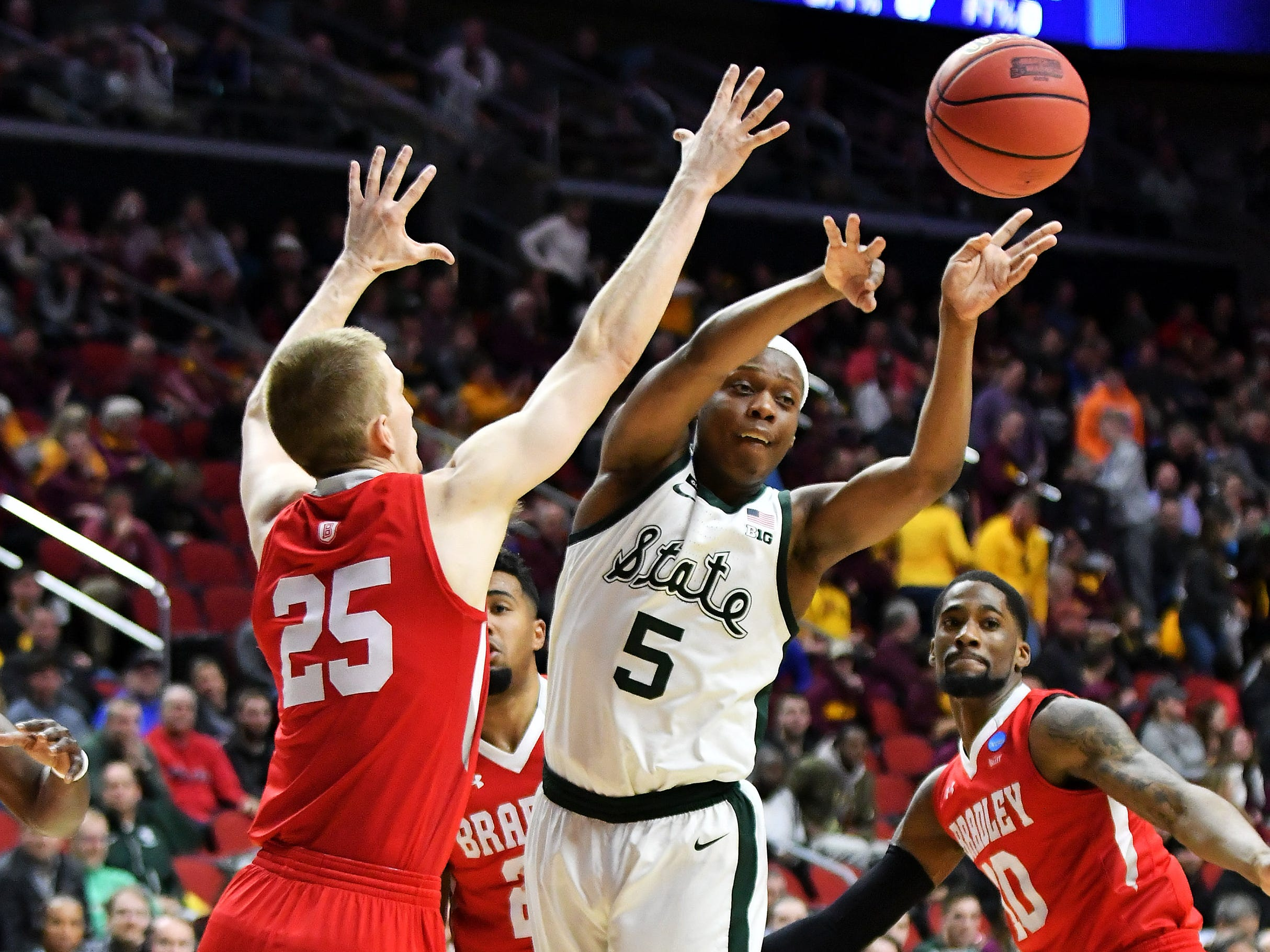 Michigan State guard Cassius Winston passes the ball under pressure from Bradley defenders in the first half.