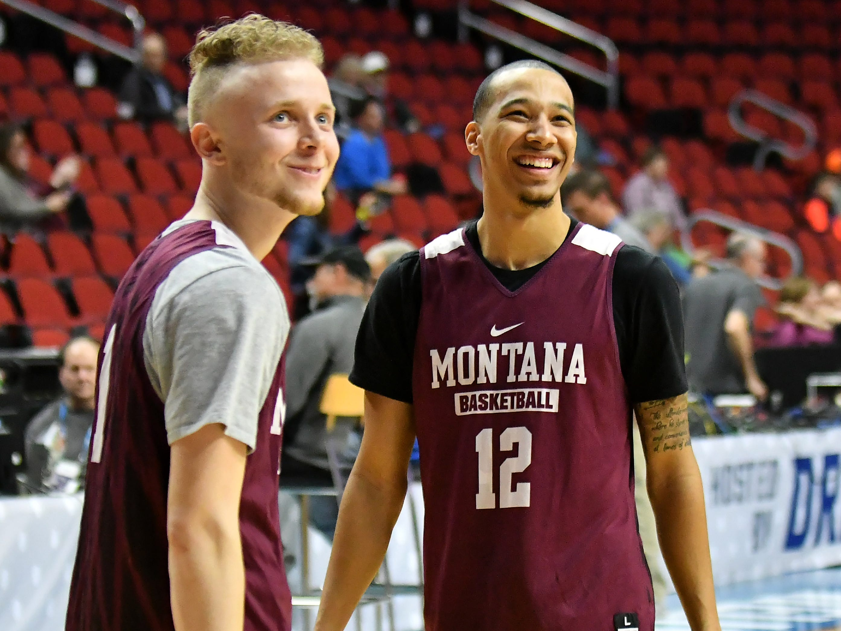 Montana guard Timmy Falls smiles with teammate Kendal Manuel (12) at practice.