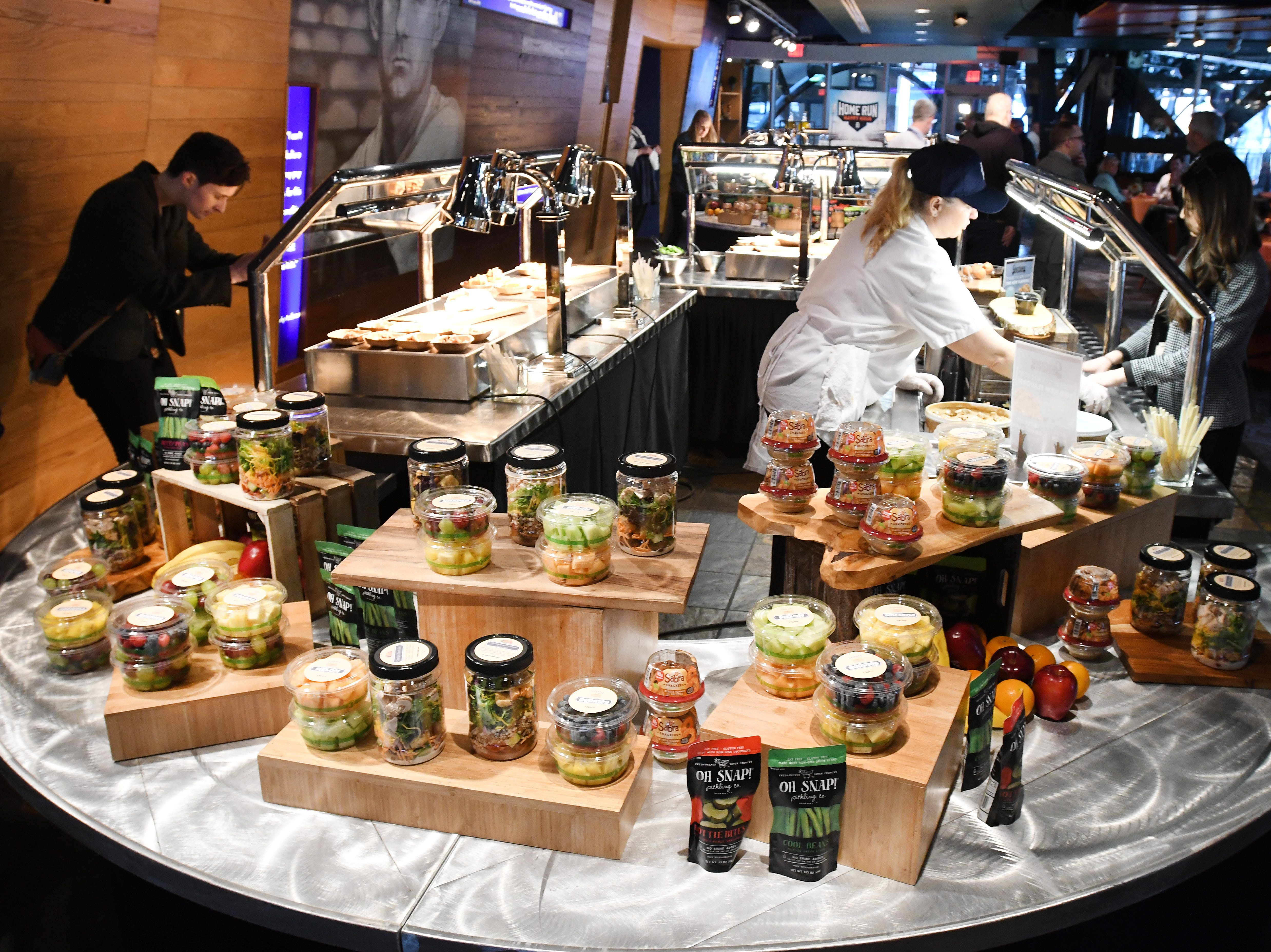 """""""Grab and Go"""" section with has Garden and Grain Salad Jars, fresh fruit cups and new healthy packaged snacks. """"What's new at Comerica Park in 2019"""" food sampling event of new menu items at the Tiger Club at Comerica Park in Detroit, Michigan on March 21, 2019.  (Image by Daniel Mears / The Detroit News)"""