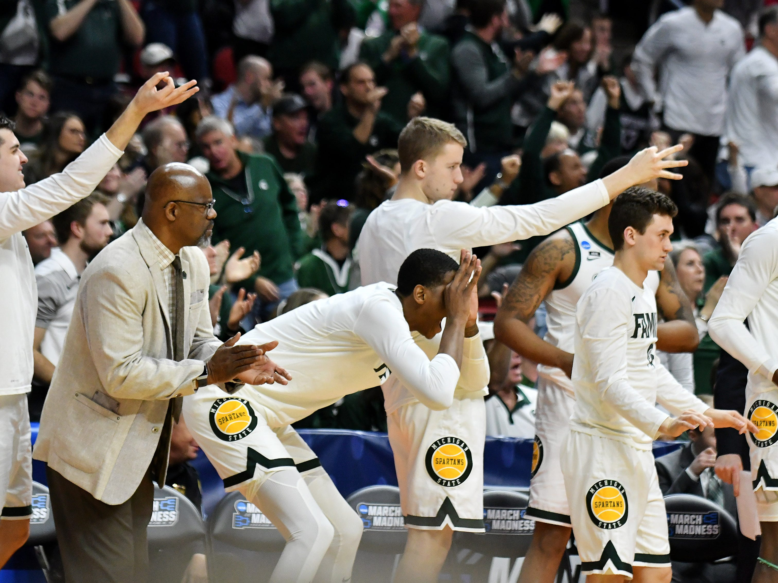 Players and staff on the Michigan State bench react after a three-pointer in the second half.