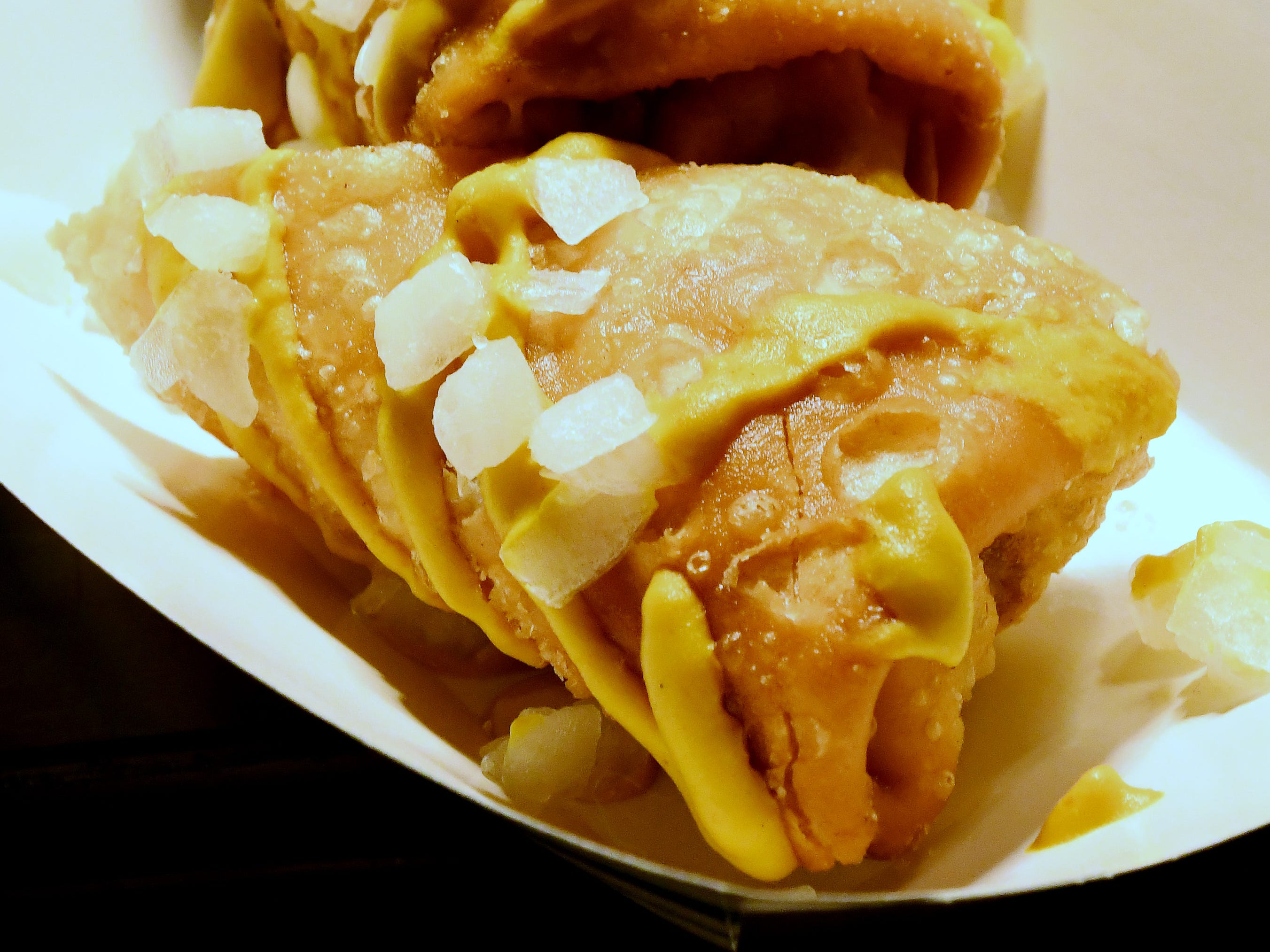 """""""Coney Dog Eggroll"""" which is a crispy egg roll filled with hot dog and chili, drizzled with classic mustard and sprinkle of diced onions."""
