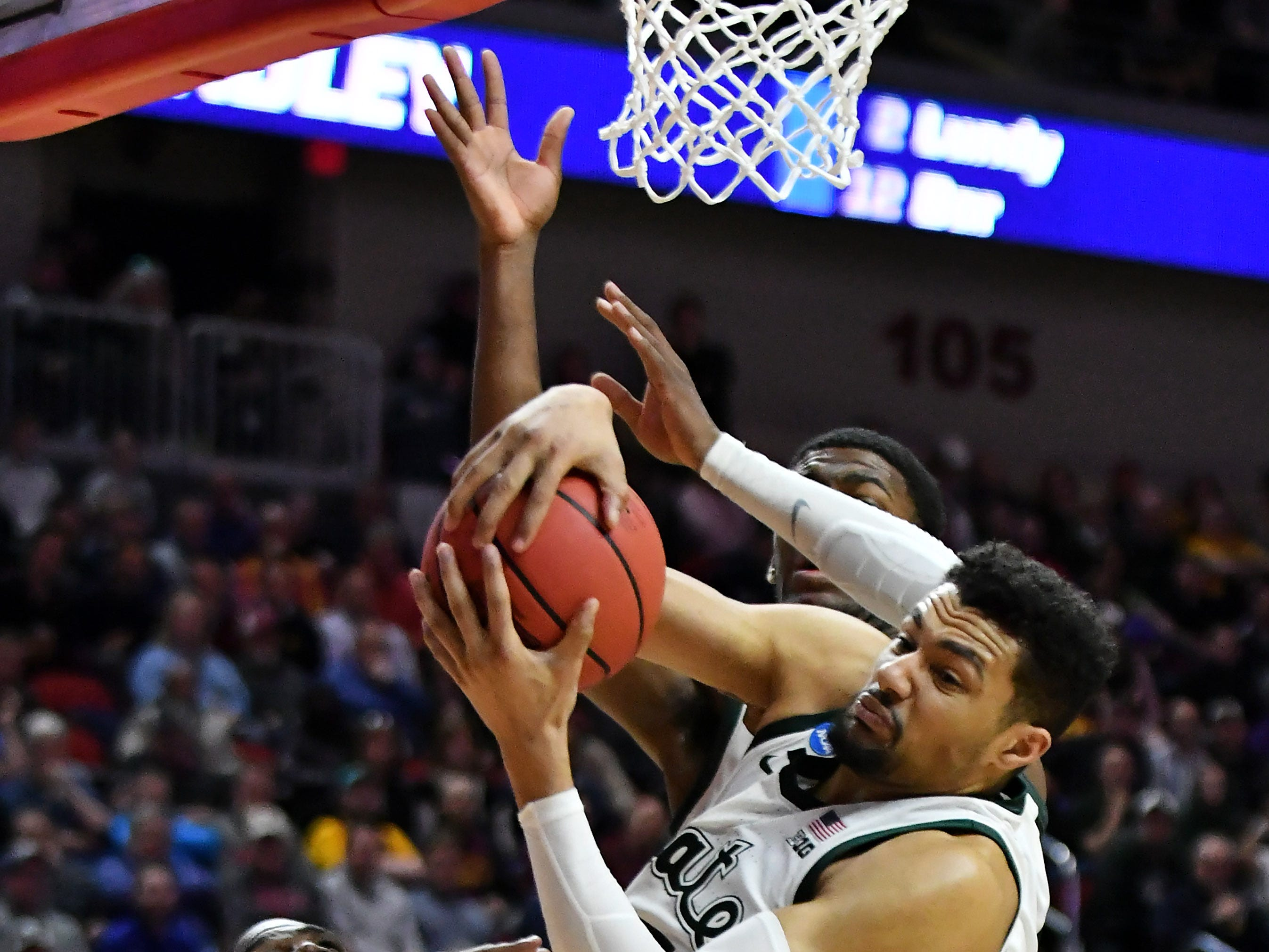 Michigan State forward Kenny Goins (25) comes down with a rebound next to Bradley guard Darrell Brown (5)  in the second half.