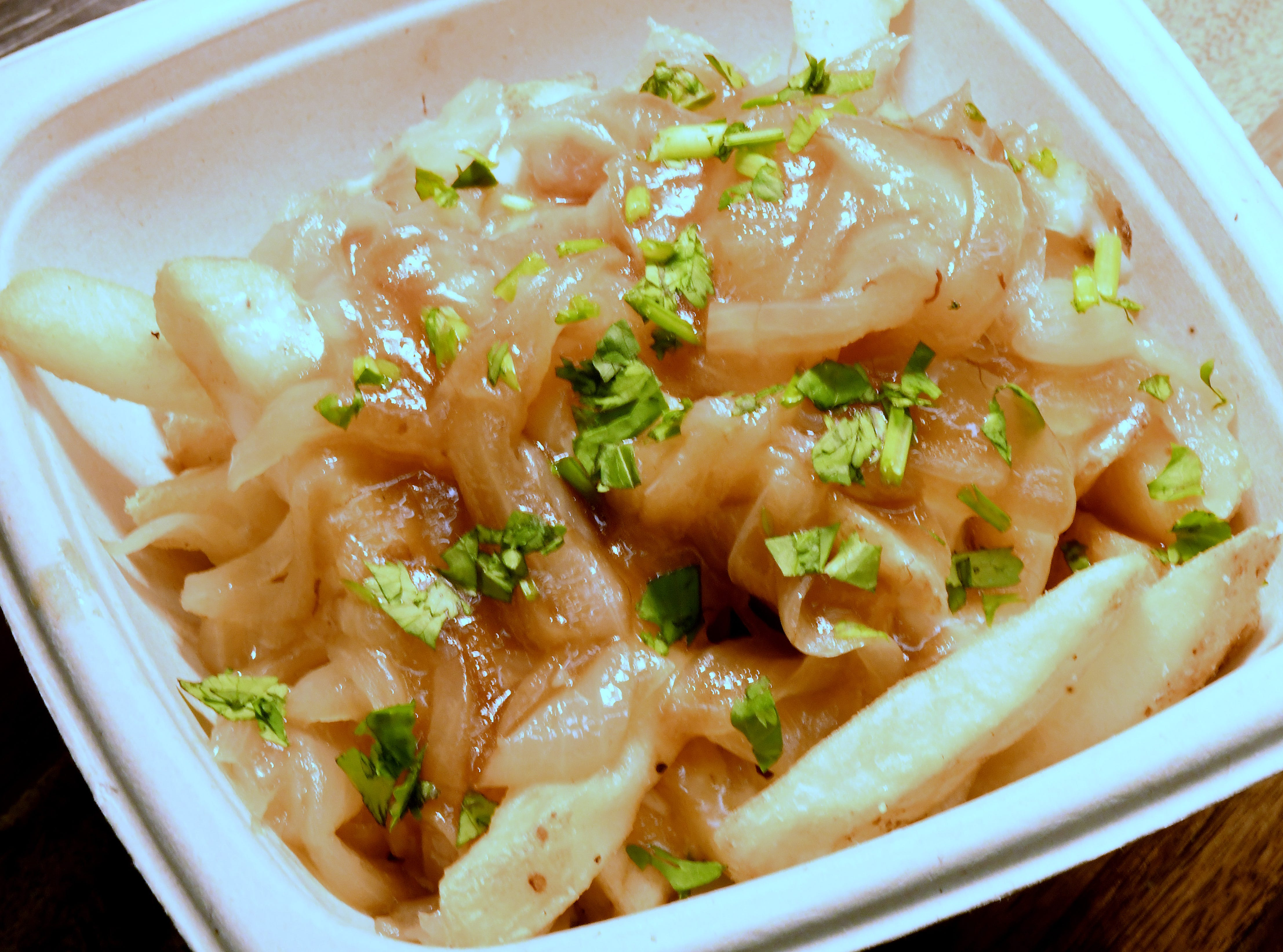 """""""French Onions topped Fries"""" consisting of crispy French fries smothered in Swiss cheese and caramelized onions and drizzled with a tangy zip sauce."""