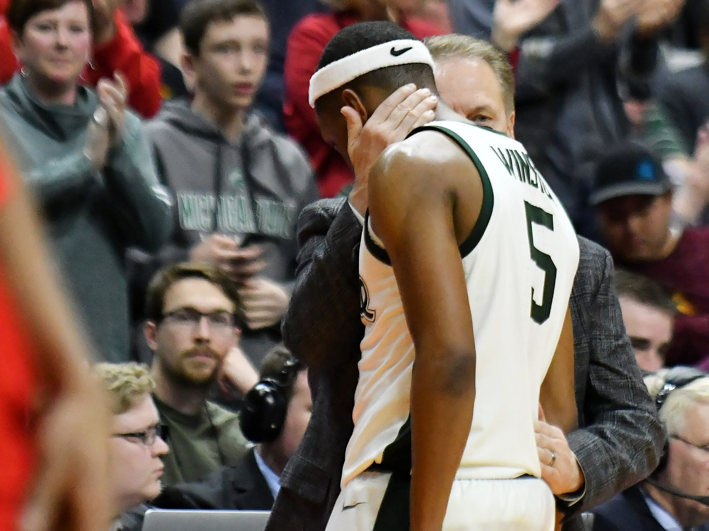 Michigan State guard Cassius Winston (5) comes out of the game and is greeted by head coach Tom Izzo late in the second half.