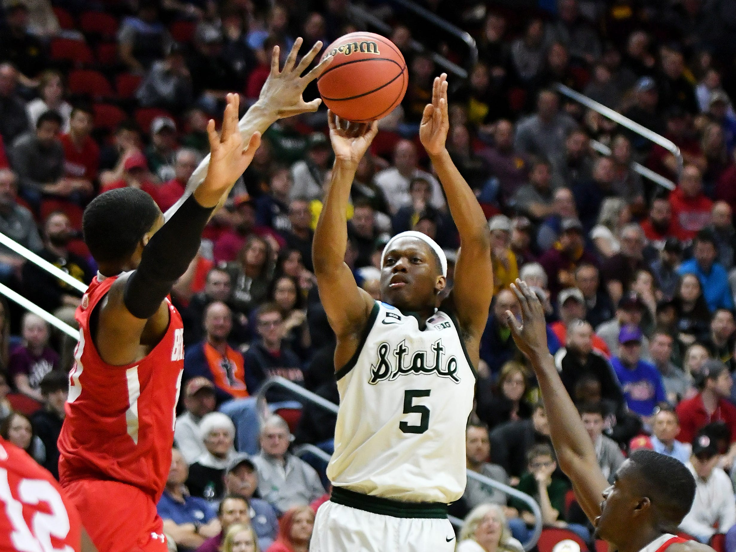 Bradley forward Elijah Childs, left, and center Koch Bar, right, defend a shot by Michigan State guard Cassius Winston (5) in the second half.