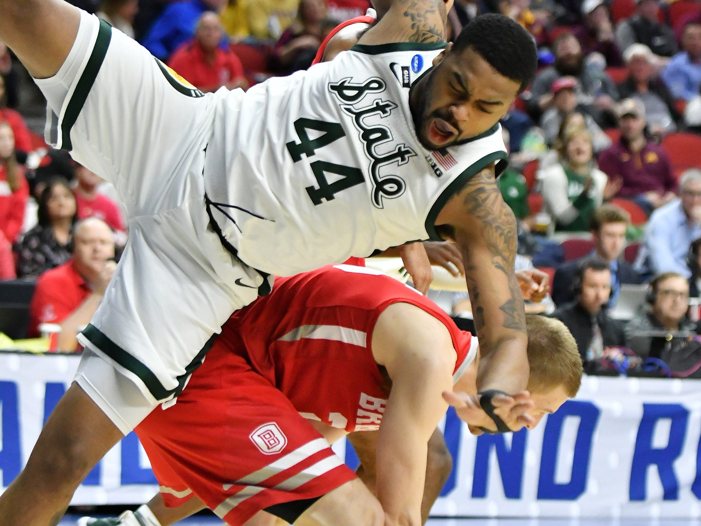 Michigan State forward Nick Ward (44) fall to the hardwood after tangling with Bradley guard Nate Kennell in the first half Thursday, March 21, 2019, at Wells Fargo Arena in Des Moines, Iowa.