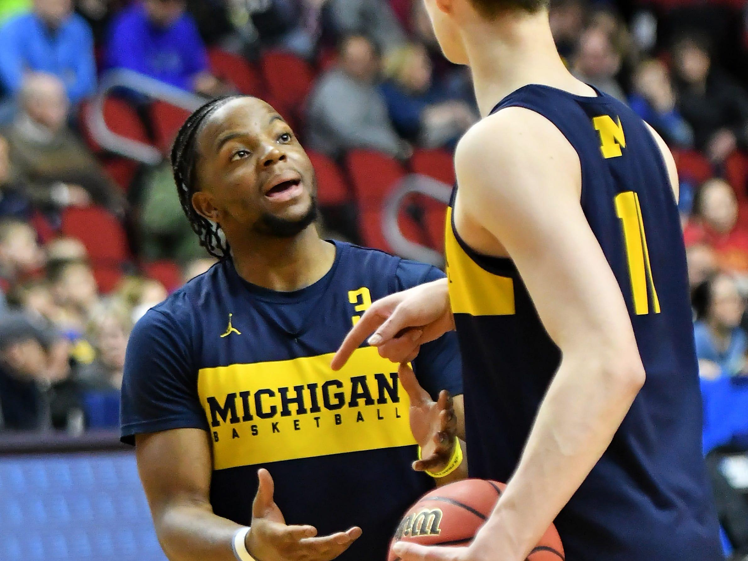 Michigan guard Zavier Simpson, left, talks with forward Colin Castleton.