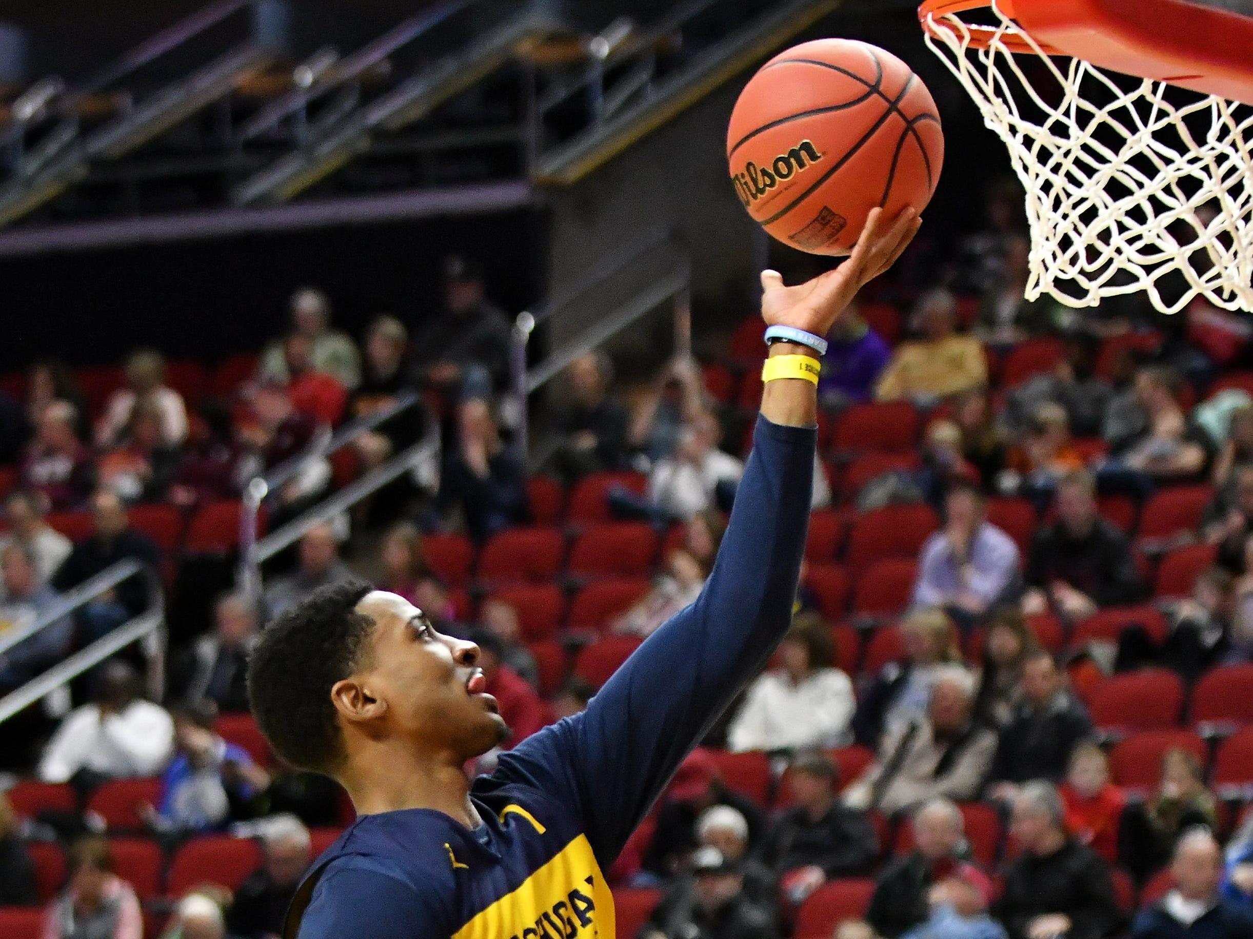 Michigan guard Charles Matthews does a layup at practice.