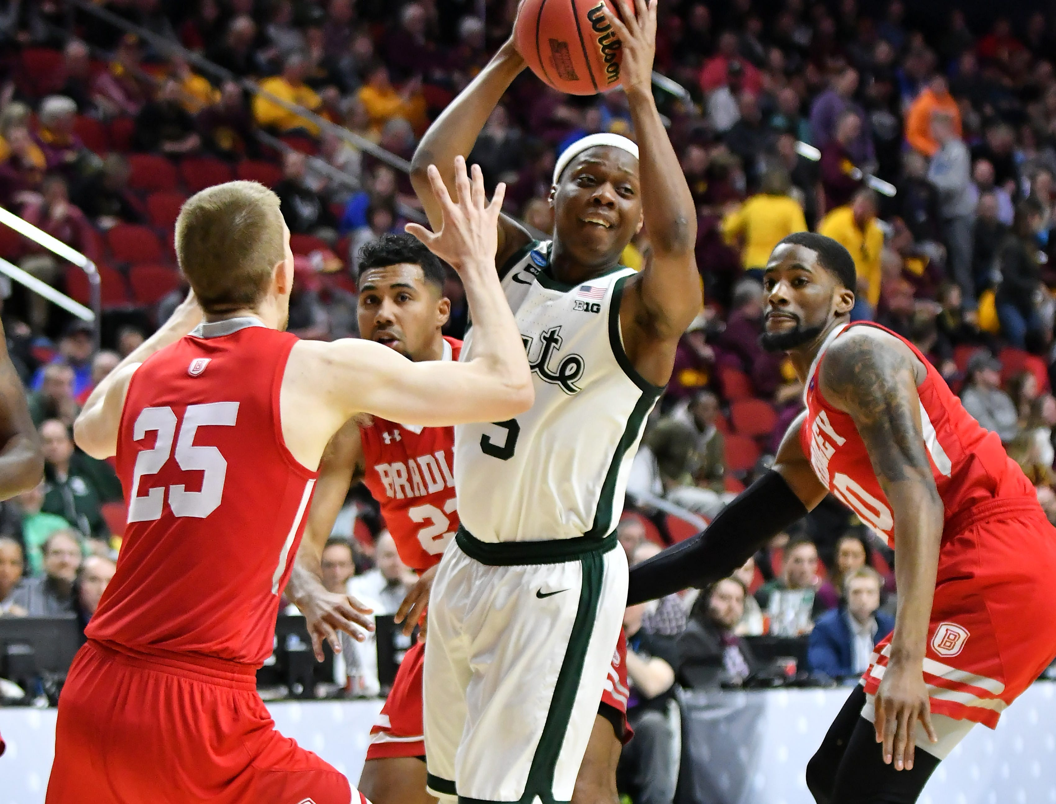 Bradley defenders, from left, Nate Kennell, Dwayne Lautier-Ogunleye and Elijah Childs converge on Michigan State guard Cassius Winston (5)  in the first half.