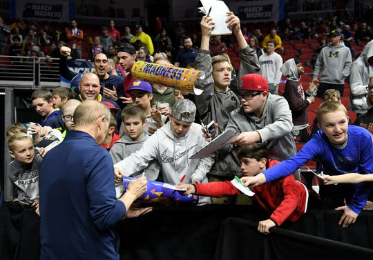 Michigan head coach John Beilein signs autographs for fans.