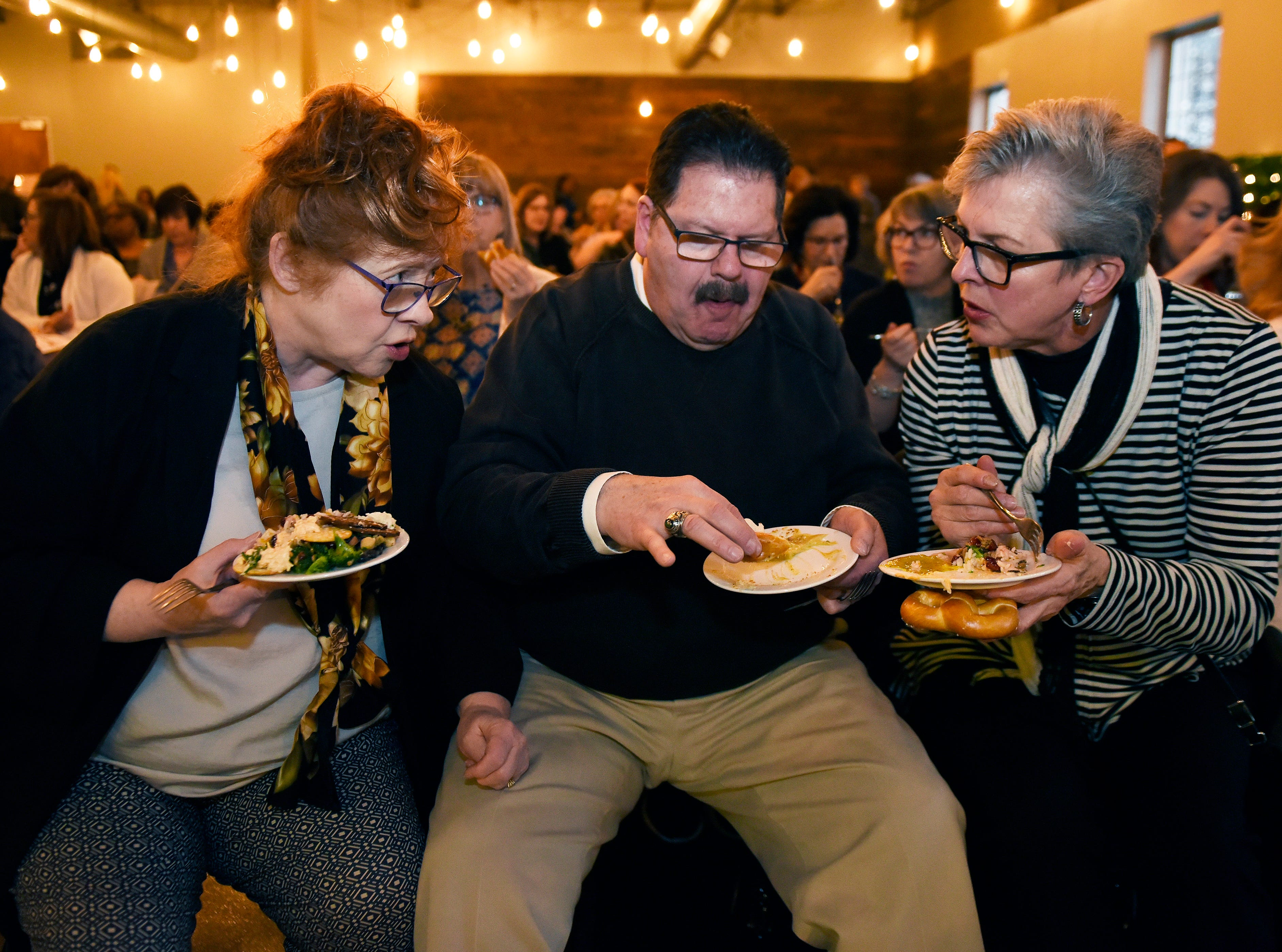 l-r, Nancy Jeffers and her husband Gary Jeffers of Northville and Louise Coleman of Novi converse while eating a dish of food prior to the start of the event.