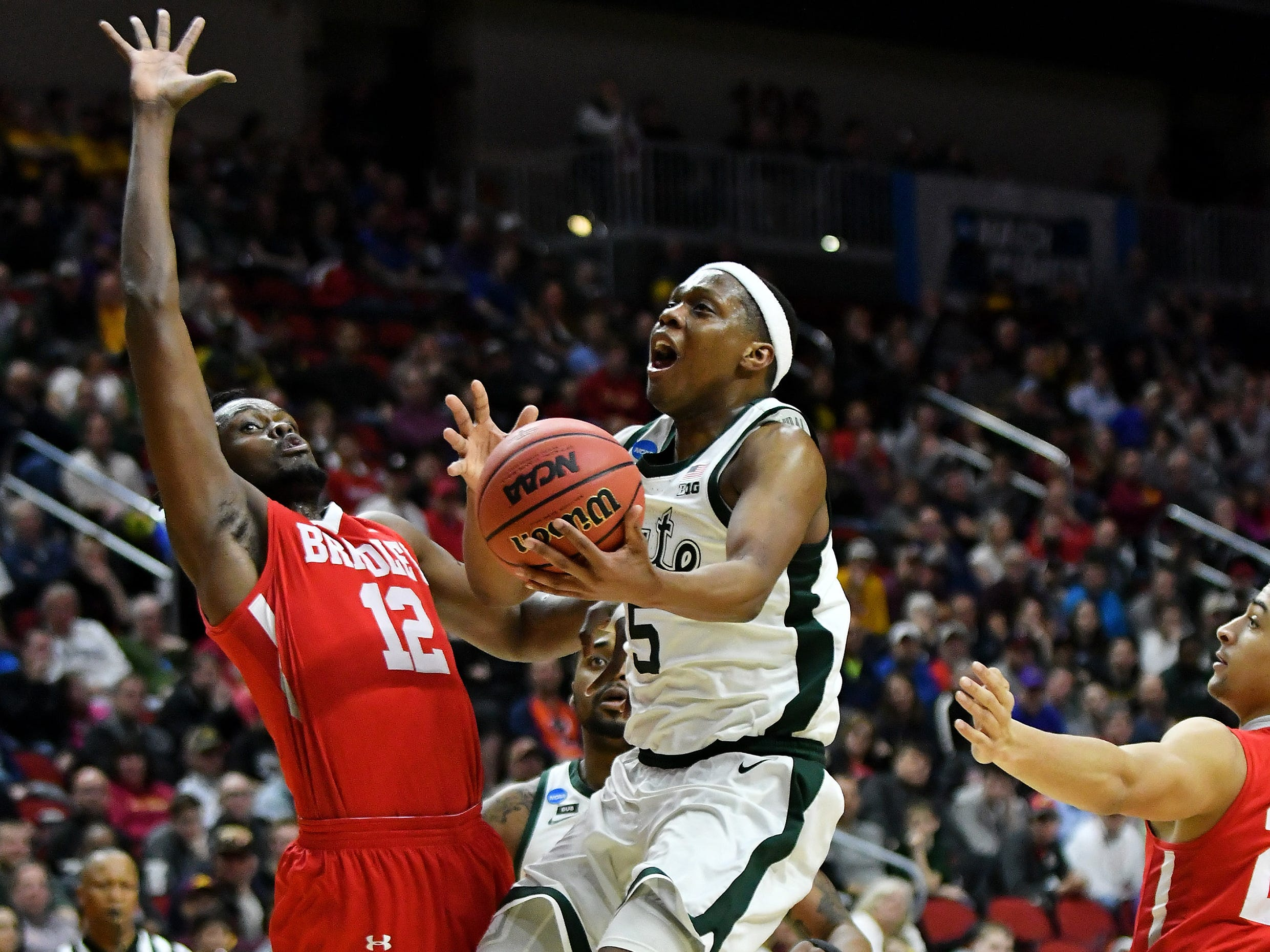 Bradley center Koch Bar (12) defends a drive by Michigan State guard Cassius Winston (5)  in the second half.