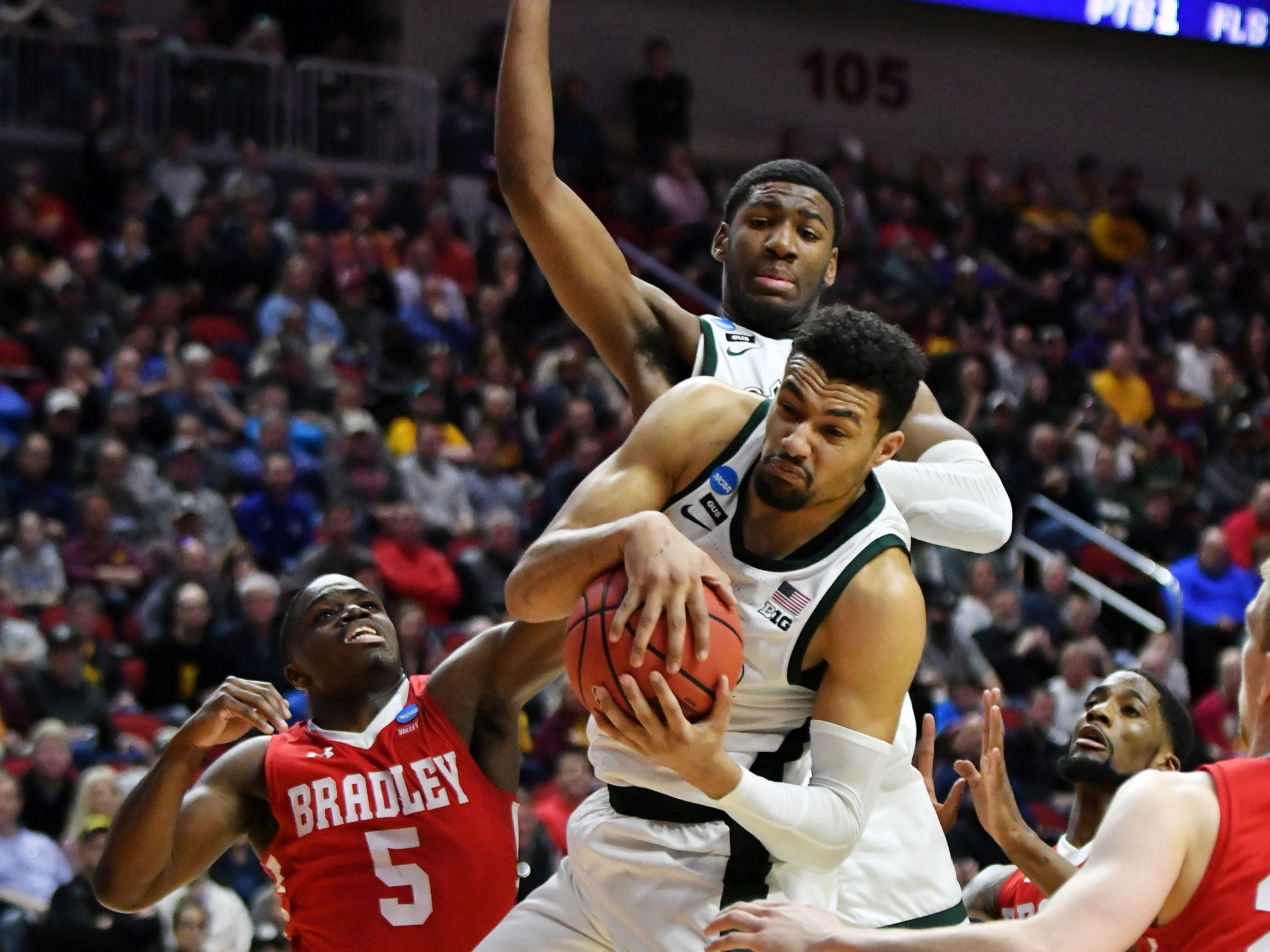 Michigan State forward Kenny Goins (25) comes down with a rebound next to Bradley guard Darrell Brown (5) in front of Michigan State's Aaron Henry, rear, in the second half.