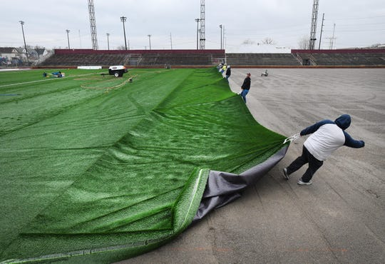 Workers from Shaw Sports Turf of Georgia pull out the sewn-together panels across the prepared surface at Keyworth Stadium.