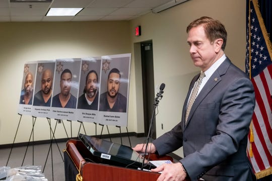 Oakland Country Sheriff Michael Bouchard stands in front a row of mugshots of five men arrested as a result of an investigation into a drug trafficking organization which was operating within Oakland County and the Metro Detroit region, during a press conference, March 21, 2019.