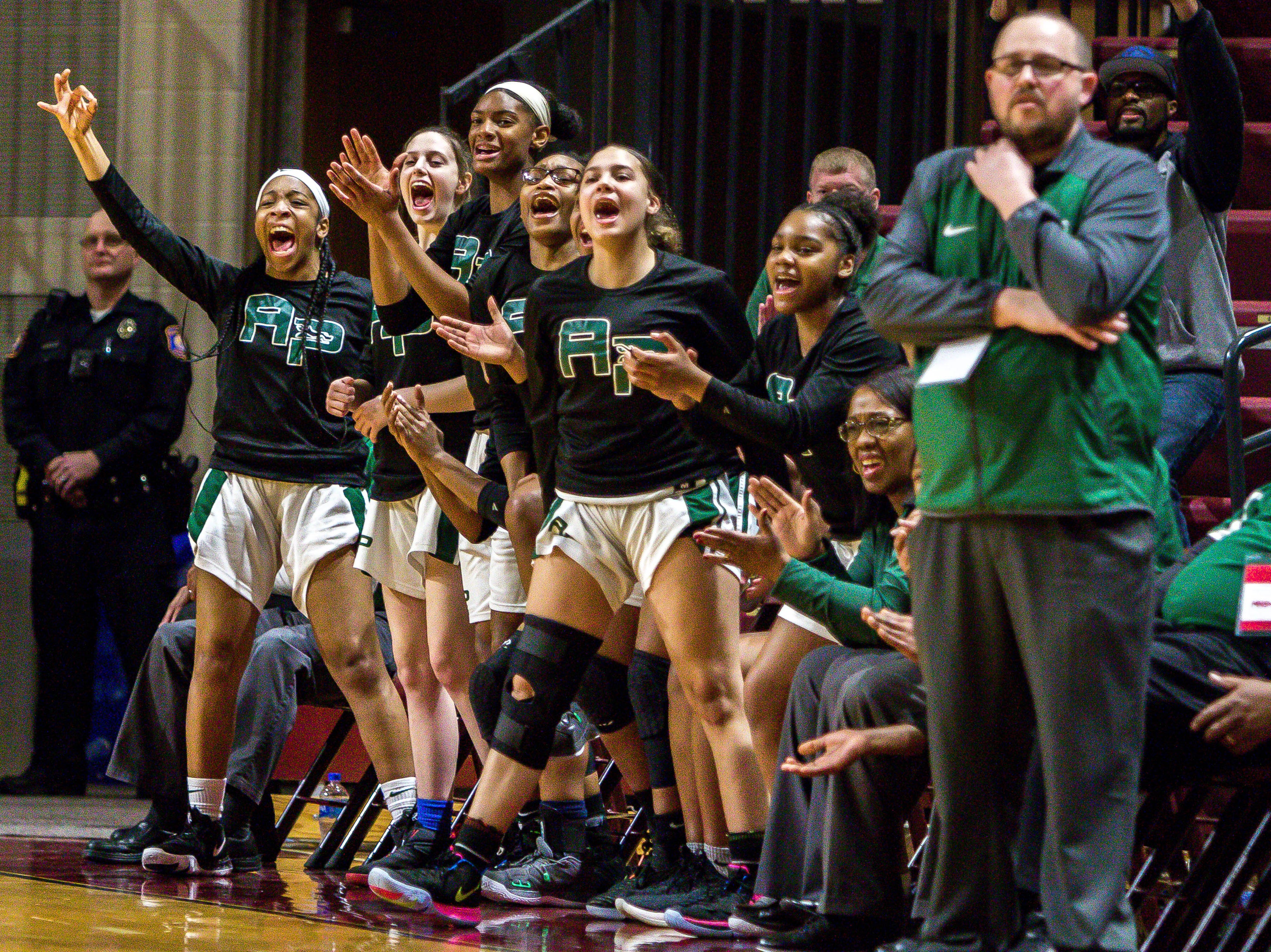 The Ypsilanti Arbor Prep bench reacts after a 3-point shot in the second half.
