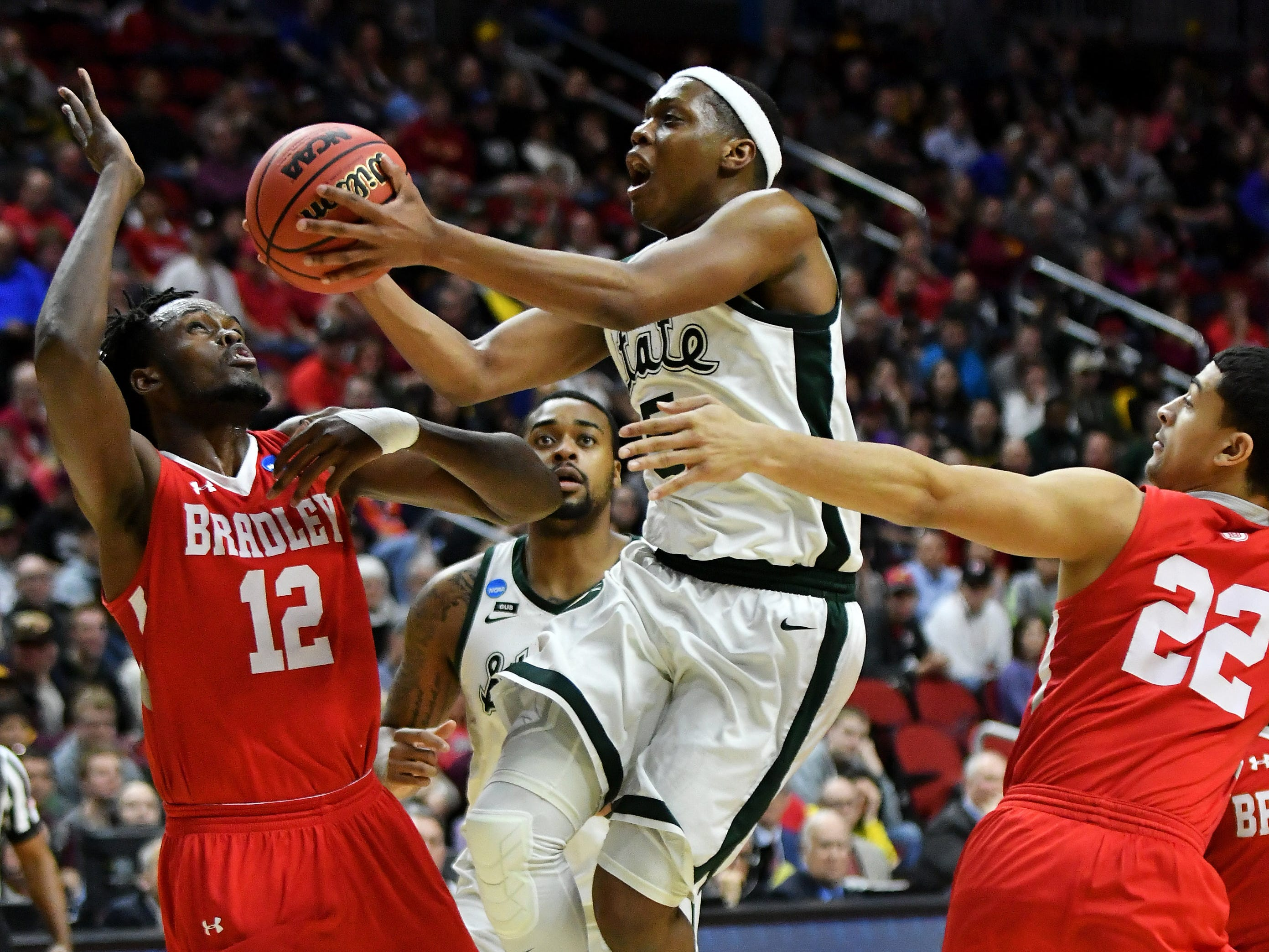 Bradley center Koch Bar (12) and Ja'Shon Henry (22)  defend a drive by Michigan State guard Cassius Winston (5)  in the second half.