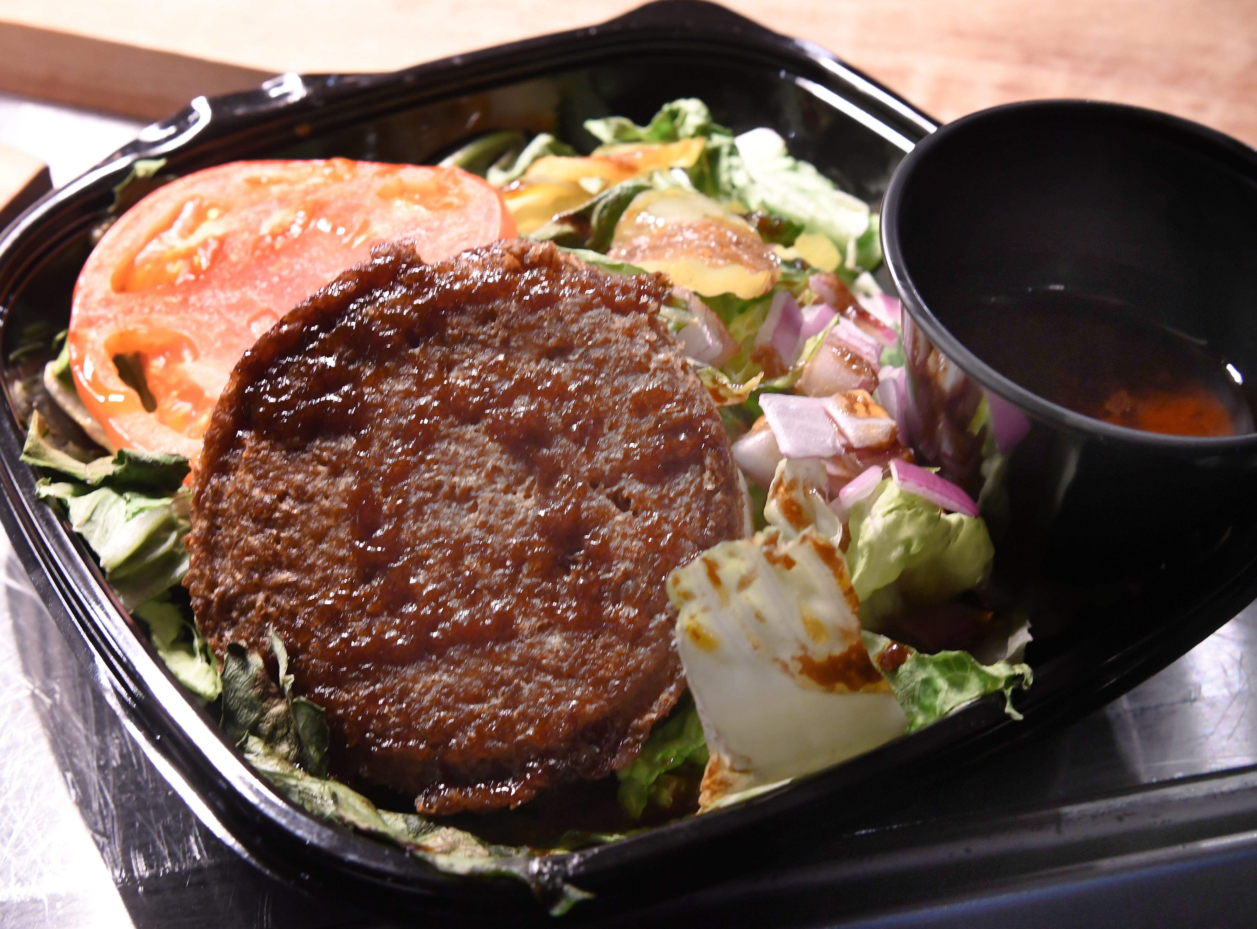 """""""Beyond Burger Bowl"""" consisting of a plant baed burger that looks and satisfies like beef on a bed of lettuce with tomatoes, onions and a pickle balsamic dressing."""