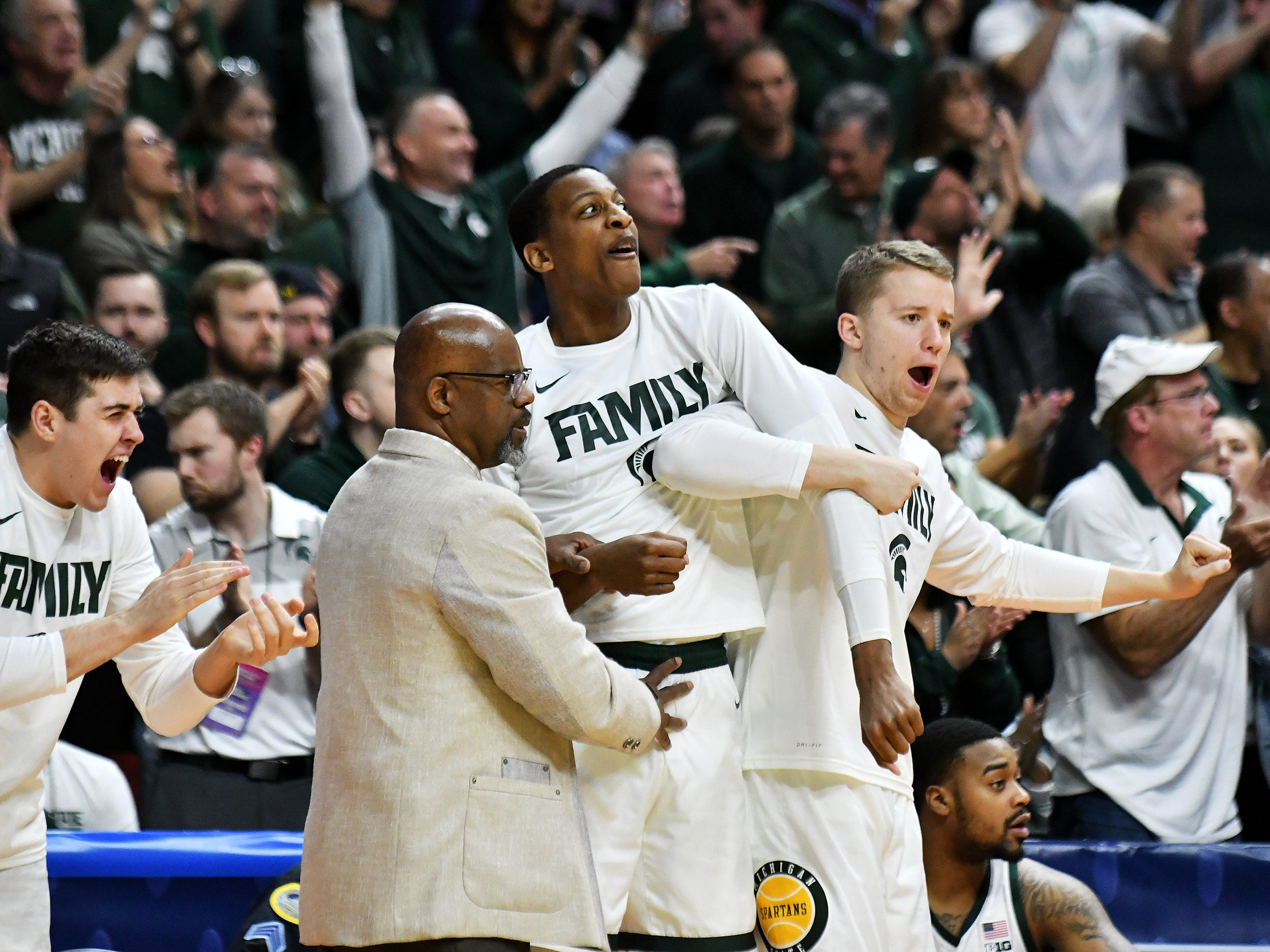 Michigan State forward Marcus Bingham Jr., center left, Thomas Kithier, right, and Conner George, left, celebrate their lead in the second half.