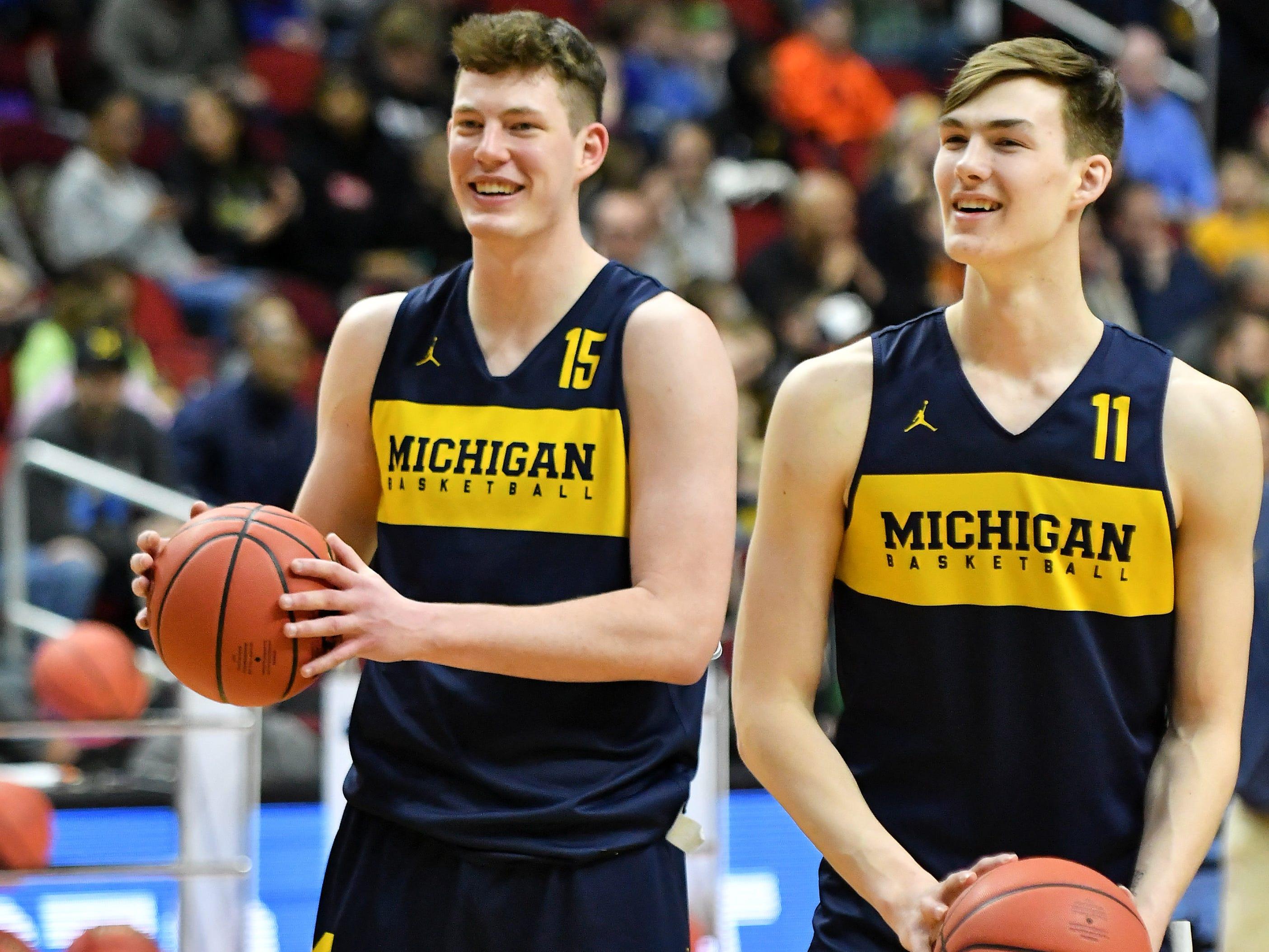 Michigan center Jon Teske, left, and forward Colin Castleton smile during practice.
