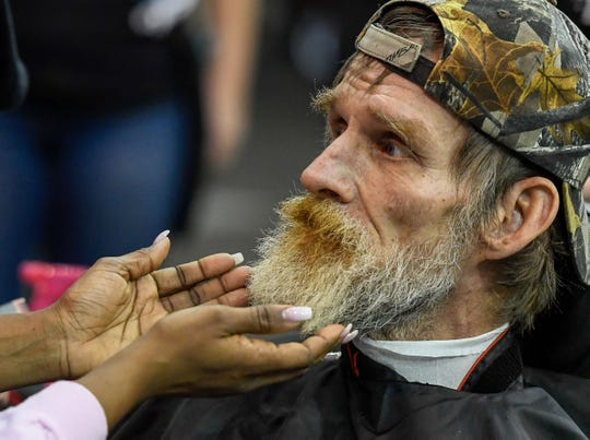Evansville resident Roger Goodridge gets his beard evaluated before getting a trim during the Homeless Connect of Southwest Indiana event where more than 70 local agencies gathered at the Old National Events Plaza to help the homeless with employment, education, housing and health screening Thursday, March 21, 2019.