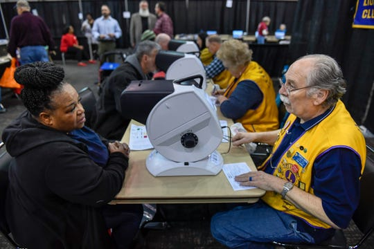 Rayetta Madison, Evansville, gets her eye examined by Don Baker with the Eastside Lions Club during the Homeless Connect of Southwest Indiana event where more than 70 local agencies gathered at the Old National Events Plaza to help the homeless with employment, education, housing and health screening Thursday, March 21, 2019.