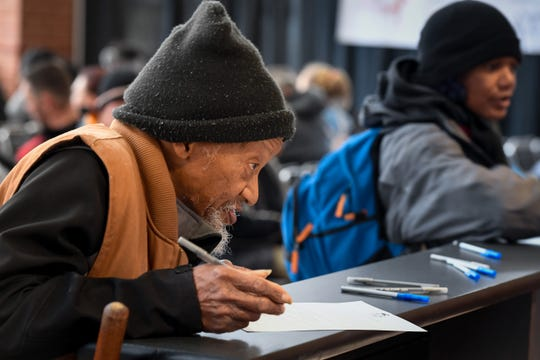 Marse Fly, Evansville, fills out a sign-in form during the Homeless Connect of Southwest Indiana event where more than 70 local agencies gathered at the Old National Events Plaza to help the homeless with employment, education, housing and health screening Thursday, March 21, 2019.