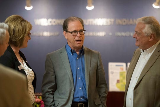 Fifth Third Bank representatives Jennifer Raibley, left and Dwight Hamilton, right, meet with Senator Mike Braun before a forum held at the Southwest Indiana Chamber office in Downtown Evansville Thursday, March 21, 2019.