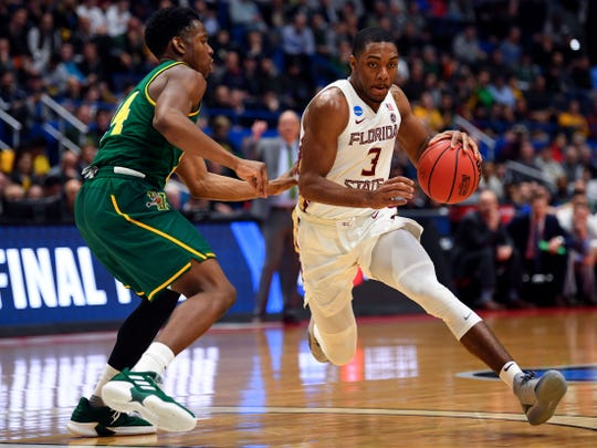 Florida State junior point guard Trent Forrest (3) drives to the basket around Vermont guard Ben Shungu (24) during the second half off a game in the first round of the 2019 NCAA Tournament at XL Center.