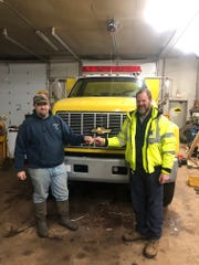 Alan Hardie, assistant chief of the LaPointe Fire Department, accepts the keys for a water tender truck from Hoyt Purinton, assistant chief of the Washington Island Fire Department. The Washington Island department offered the loan of the truck after the LaPointe fire station was destroyed.