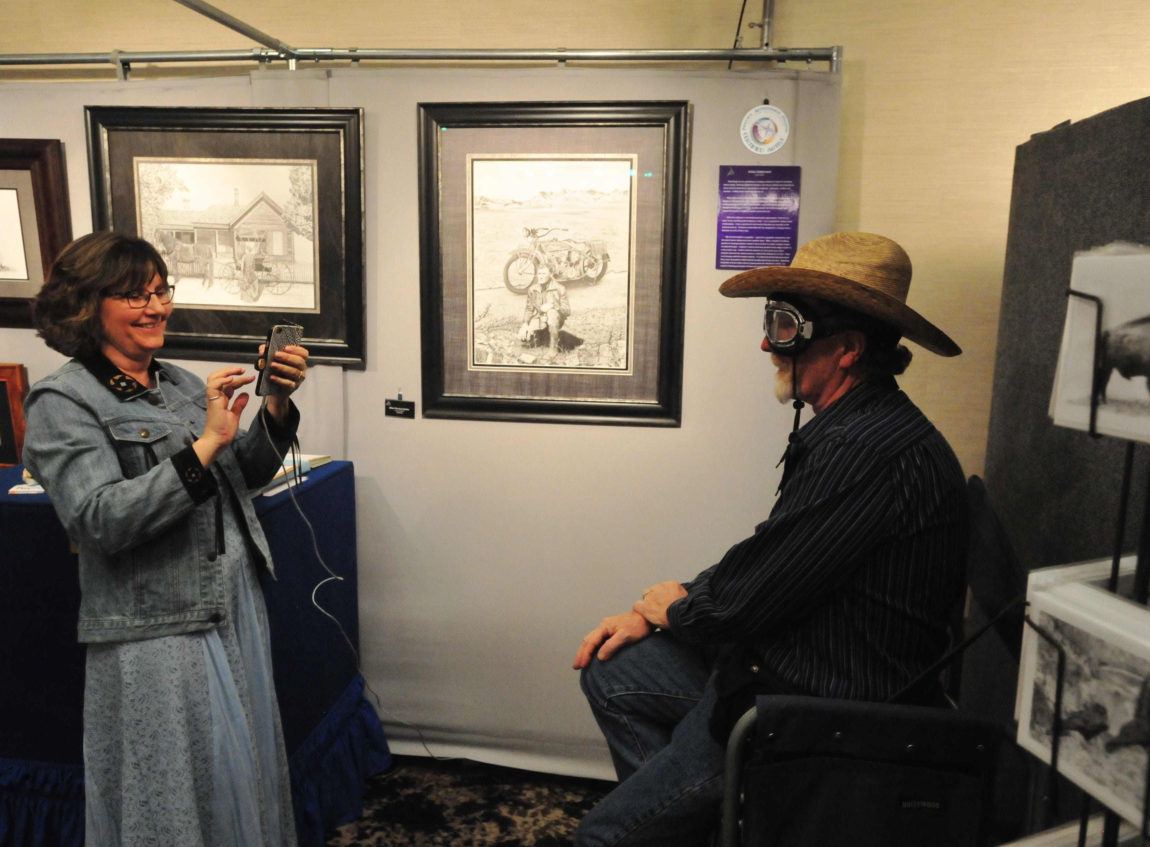 Debbie Cain snaps a photo of her husband, artist Lynn Cain, wearing his replica aviator goggles at the Wild Bunch Art Show in the Hampton Inn, Thursday.  Cain used the goggles in one of his pencil drawings of a man and his motorcycle.