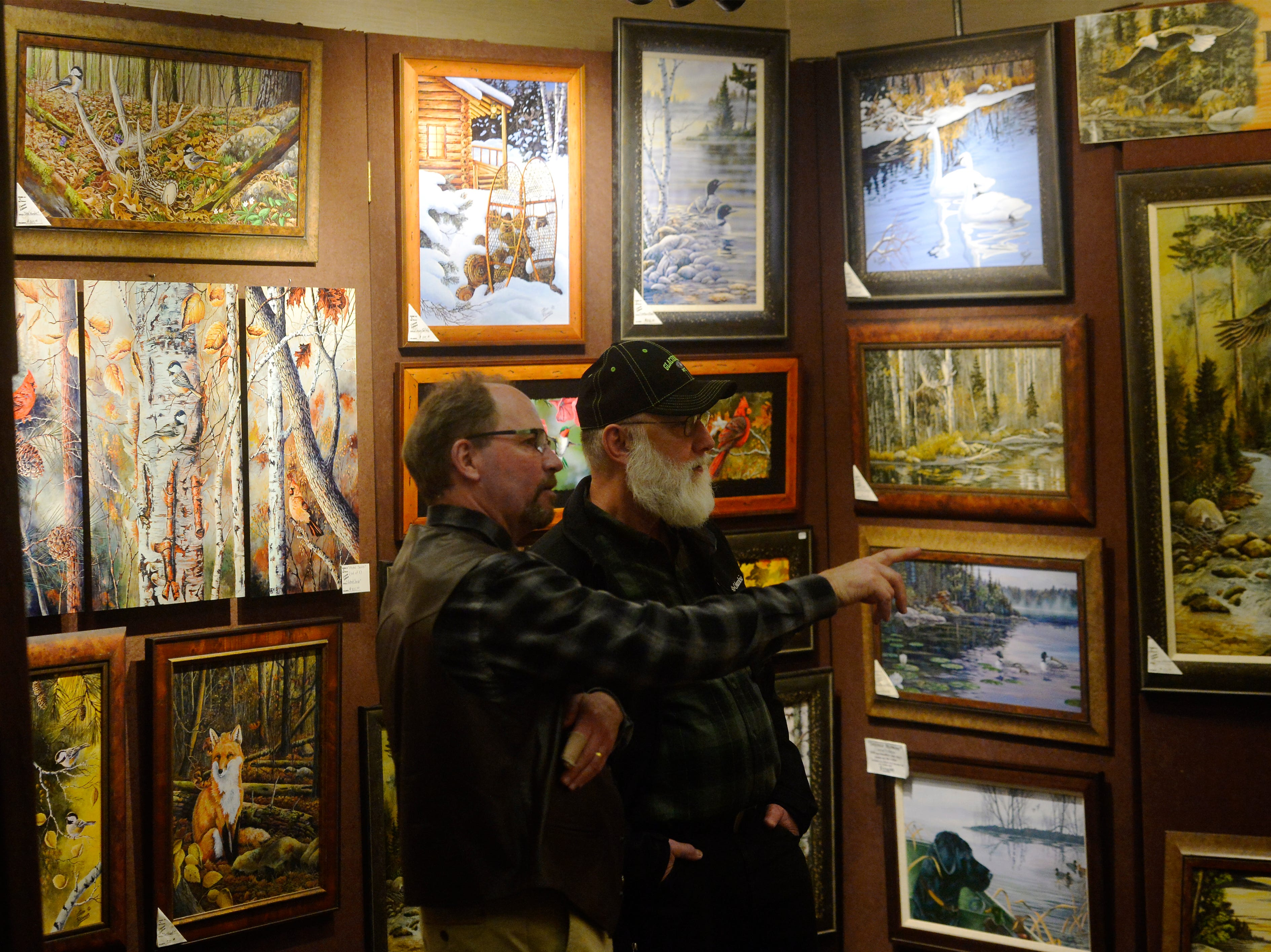 Artist Jeff Renner talks with Bill Tacke at the Wild Bunch Art Show in the Hampton Inn.