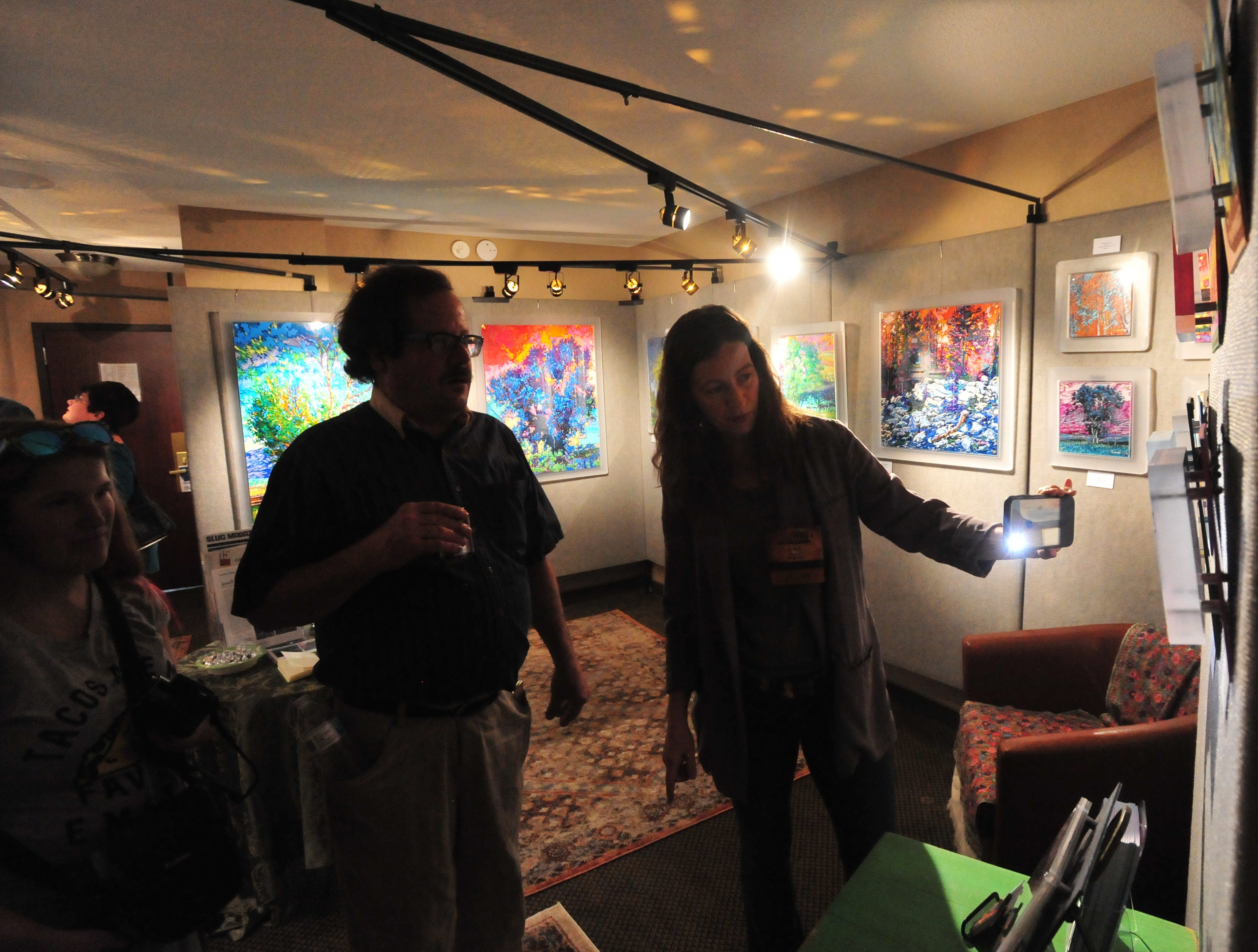 Artist Janell James talks about her work in her room at the Out West Art Show in the Heritage Inn.