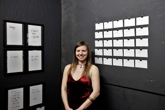 Eileen Laskowski posing beside her art at Wednesday night's opening show.