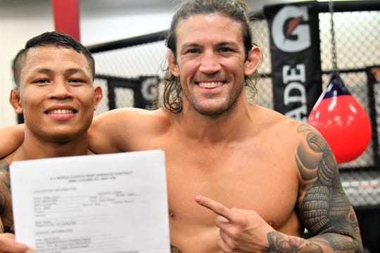 "Guam fight fan favorite Ricky ""2 Slick"" Camp, at left, proudly displays his latest contract with X-1 World Events to fight for the bantamweight title in April in Hawaii. Training partner and manager JJ Ambrose negotiated the deal and surprised Camp with a fight date earlier this week."
