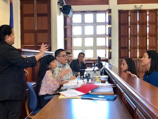 Speaker Tina Muna Barnes, left, gestures as she and legislative counsel Julian Aguon confer with Sen. Regine Biscoe Lee and Vice Speaker Telena Nelson, right, during a short break in the March 21, 2019 session.