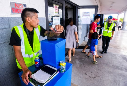 DR Safety Consultant fire watch safety officer Mark Malicat, left, uses a hand counter to keep track of the number of customers who exit the Department of Revenue and Taxation building as fellow safety officer Edward Corpuz is positioned at the door on Thursday, March 21, 2019.